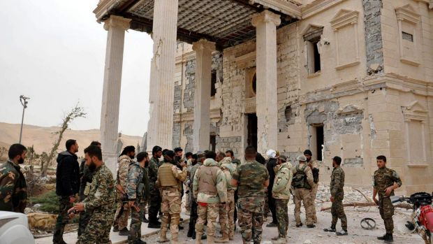 Syrian soldiers outside a damaged palace in Palmyra.