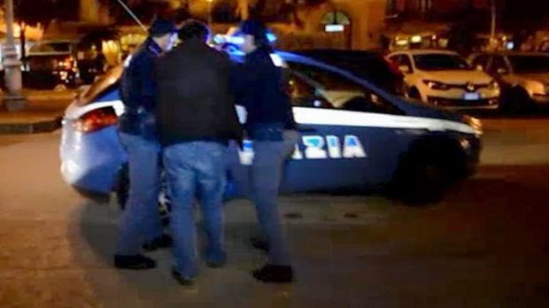 Italian police escort a man into a police car in the southern city of Salerno on Sunday. Police identified the man as an ...