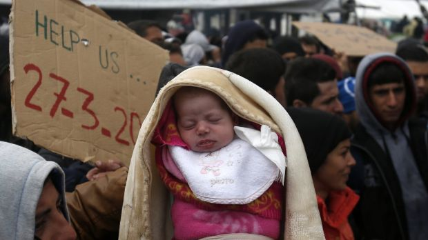 A migrant holds a baby during a protest demanding the opening of the border between Greece and Macedonia on Sunday.