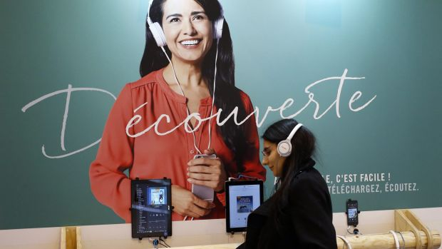 A woman listens with headphones to an audiobook during a visit to the Paris International Book Fair, held at the Porte ...