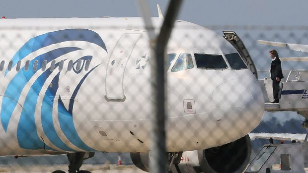 A crew member of the hijacked EgyptAir aircraft on the passenger boarding stairs after landing at Larnaca airport on Tuesday.