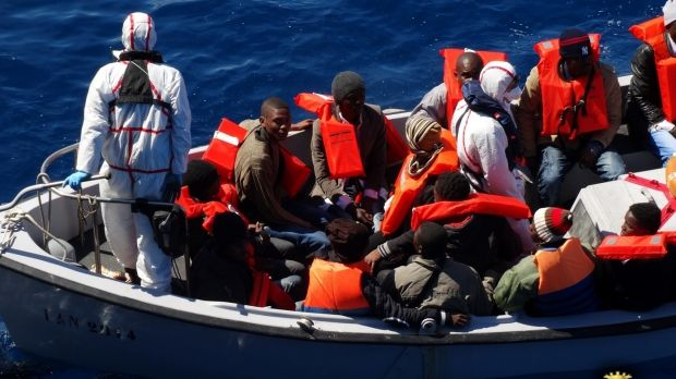 Rescued migrants wear life-jackets as they sit in an Italian navy's boat in the Sicilian Channel, Mediterranean Sea, on ...