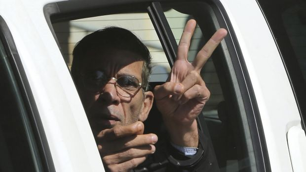 Seif Eldin Mustafa flashes the victory or peace sign as he leaves a court in Cyprus on Wednesday.