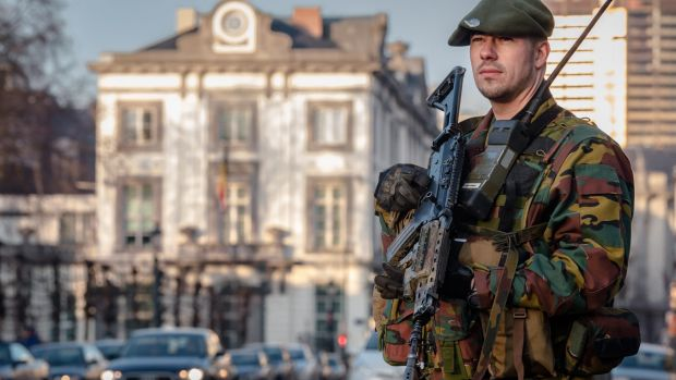 A Belgian para-commando patrols near the office of the prime minister in Brussels.