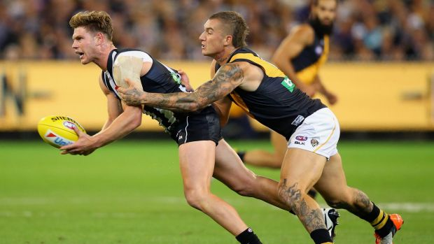 Taylor Adams of the Magpies handballs whilst being tackled by Dustin Martin of the Tigers.