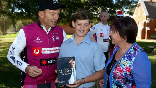 Tony Abbott hands out a copy of his book Battlelines during his Pollie Pedal fundraiser.