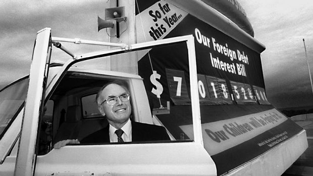 Former prime minister John Howard with the 'debt truck' on the forecourt of Parliament House.