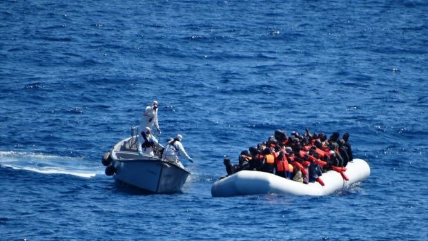 The Italian Navy approach a dinghy filled with migrants in the Mediterranean Sea in March.