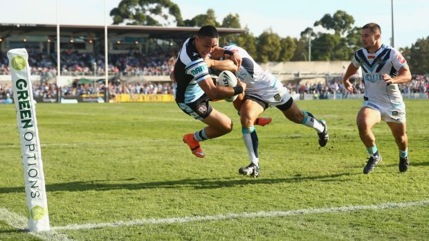 What a put down: Valentine Holmes of the Sharks is tackled as he scores try in the corner.