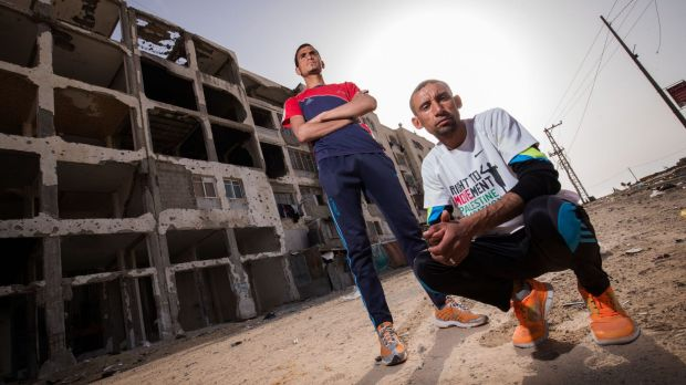 Nader al-Masri (right) and Anas al-Masri  outside a building destroyed by Israeli bombardment in the Gaza Strip town of ...
