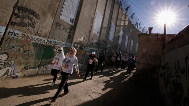 The Palestine Marathon's route alongside the Israeli-built separation wall near the occupied West Bank city of Bethlehem ...