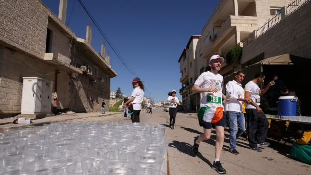 A competitor sports the Irish flag near a drinks station during this year's Palestine Marathon.