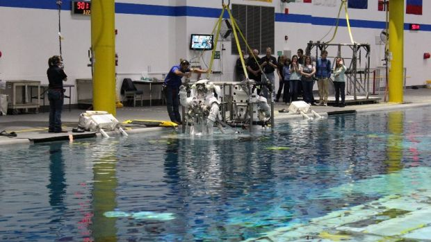 Astronauts are lowered into a pool at NASA's Neutral Buoyancy Lab.