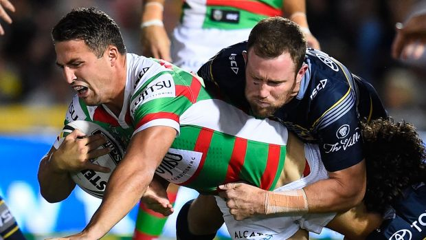 Struggling: Sam Burgess of the Rabbitohs is tackled by Gavin Cooper and Jake Granville.