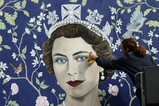 Workmen install a new mural by Frederick Wimsett, of Britain's Queen Elizabeth II to mark her 90th birthday ...