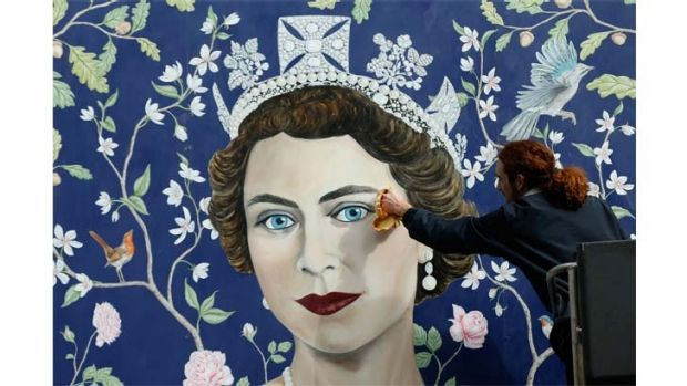 Workmen install a new mural, by Frederick Wimsett, of Queen Elizabeth II to mark her 90th birthday celebrations in ...