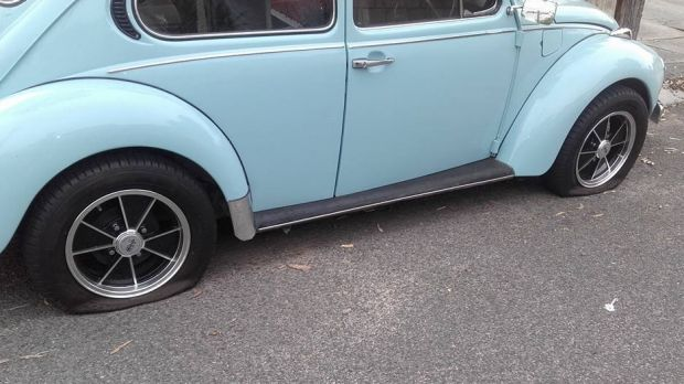 A Volkswagen Beetle with two slashed tyres.