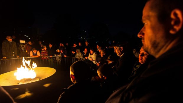 Crowds gather around the eternal flame at last year's dawn service in Melbourne.