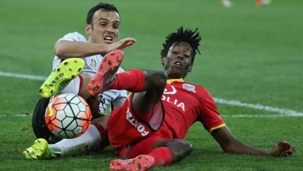 Mark Bridge, of the Wanderers, challenges Bruce Kamau, of Adelaide United, during their  A-League grand final match.