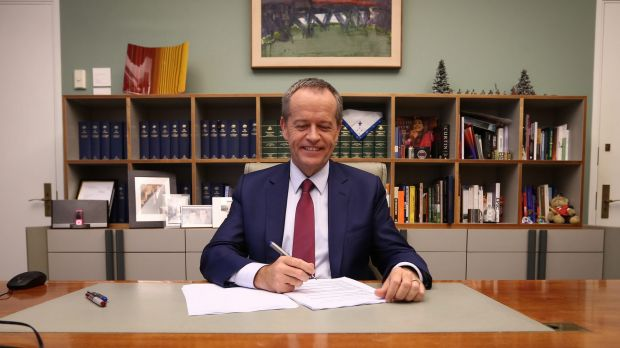 Opposition Leader Bill Shorten poses for photos in his office before delivering his budget reply speech.