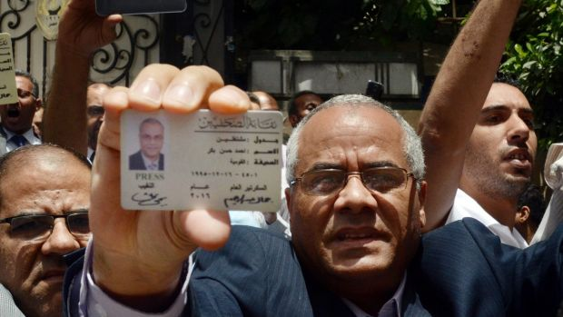 Egyptian-American journalist Ahmed Bakr shows his ID as he and others are blocked from entering a protest near the Press ...