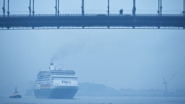 A cruise ship travels through the harbour on the city's third smoky morning.