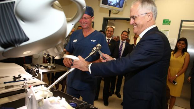 Prime Minister Malcolm Turnbull looks at a hip joint replacement robot during a hospital visit.