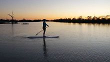 Jenna Brook stand-up paddle boarding in a billabong near Birdsville