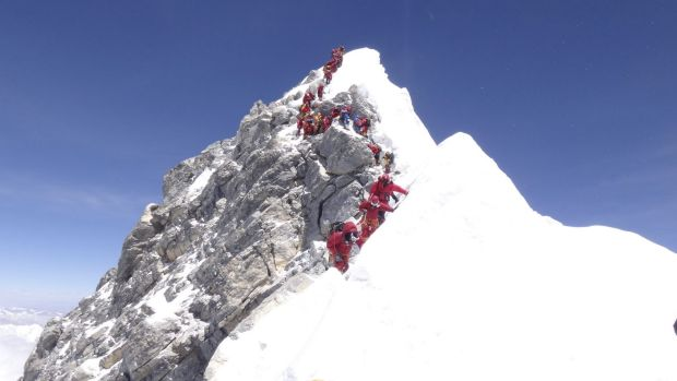 A conga line of climbers approaches the congested Hillary Step after reaching the summit of Mount Everest.