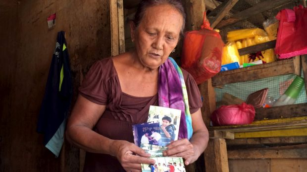Clarita Alia, 62, in Davao, holds up photographs of four teenage sons killed by vigilantes - she blames Philippine ...