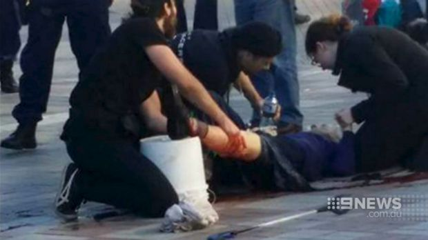 An injured bystander is treated after being caught in crossfire when police shot at Jerry Sourian at Westfield Hornsby.