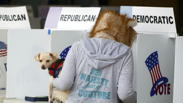 A resident wears a mask and holds a dog while voting during the presidential primary election at the Venice Beach ...