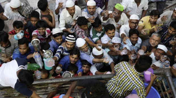 Indian Muslims jostle for drinks distributed at Nakhoda Mosque after breaking their fast in Kolkata, India, on Tuesday.