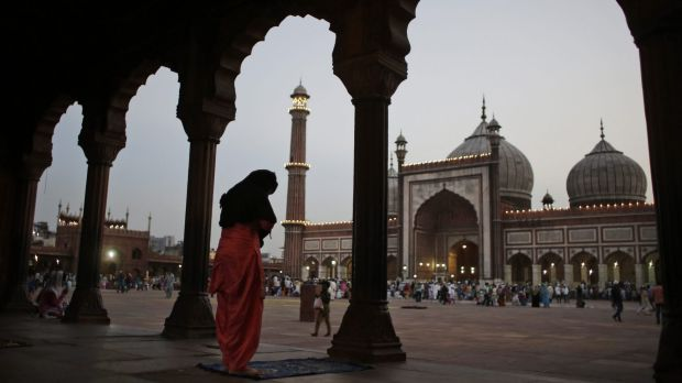 An Indian Muslim woman performs a prayer after breaking her fast on the first day of the holy fasting month of Ramadan ...
