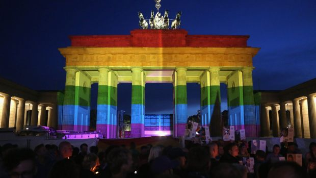 The Brandenburg Gate in Germany is seen with a rainbow flag projected onto it during a vigil for victims of the Orlando, ...