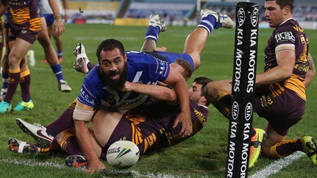 Gymnastic move: Sam Kasiano of the Bulldogs gets across the line at ANZ Stadium.