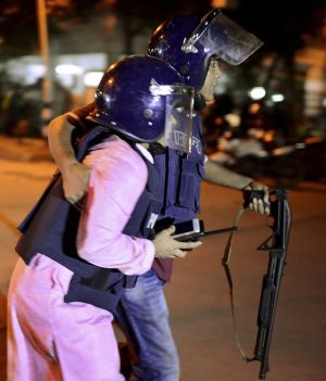 A member of Bangladeshi security personnel is taken for medical attention after gunmen attacked a restaurant  in a ...