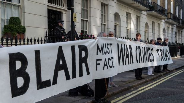 Protesters hold up a banner reading 'Blair must face war crimes trial' outside the London home of former British prime ...