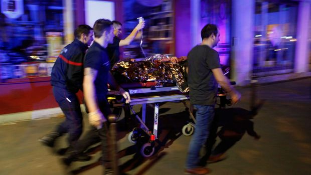 A person is being evacuated after a shooting, outside the Bataclan theater in Paris, in which 130 people died.