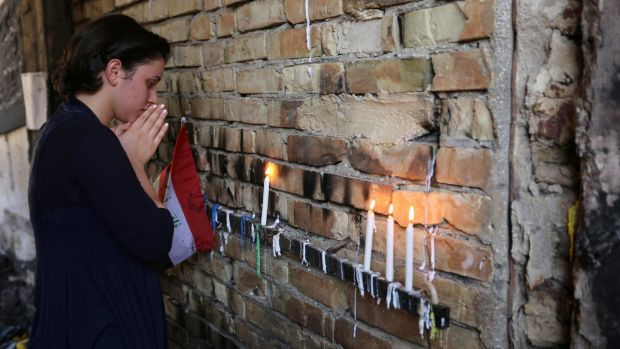 Iraqi woman prays and lights candles for the bombing victims at the scene of Sunday's massive truck bomb attack in ...