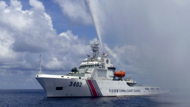 A Chinese Coast Guard boat sprays a water cannon at Filipino fishermen near Scarborough Shoal in the South China Sea ...