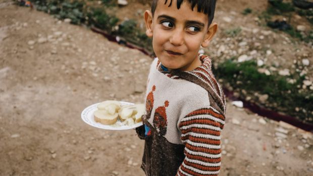 A Syrian boy walks in Kawergosk refugee camp in northern Iraq carrying a plate with boiled potatoes.