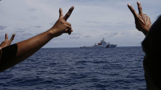 Philippine crewmen gesture towards a Chinese ship in the South China Sea