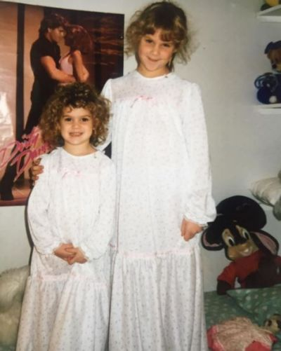 Amy Schumer shared this throwback snap with her younger sister, Kim Caramele, standing in front of a <i>/Dirty ...