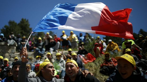 A man waves a French flag during stage twelve of the Tour de France in Montpellier.
