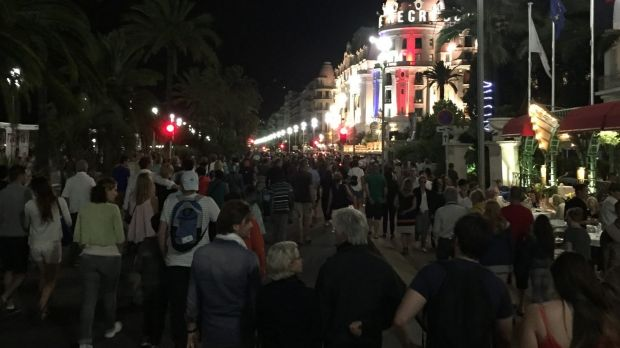 Crowds walk down the Promenade des Anglais moments before a truck fatally hits 84 people.