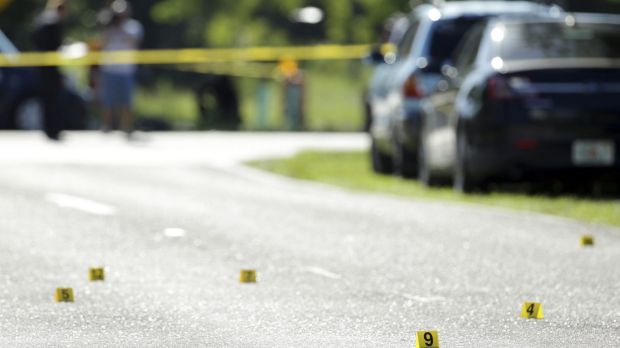 Evidence markers are placed on the street at the scene of the deadly shooting outside of the Club Blu.