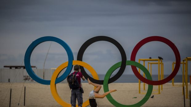 Visitors take photographs in front of the Olympic Rings at Copacabana beach in Rio de Janeiro during the 2016 Games.
