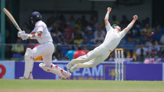 Edged: Mitchell Marsh flings himself at a shot from Dinesh Chandimal.