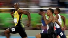 Smile for the camera: Usain Bolt competes in the men's 100m semi-final.